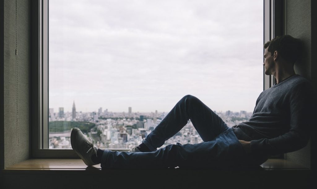 boys names that mean alone - man sitting in front of window